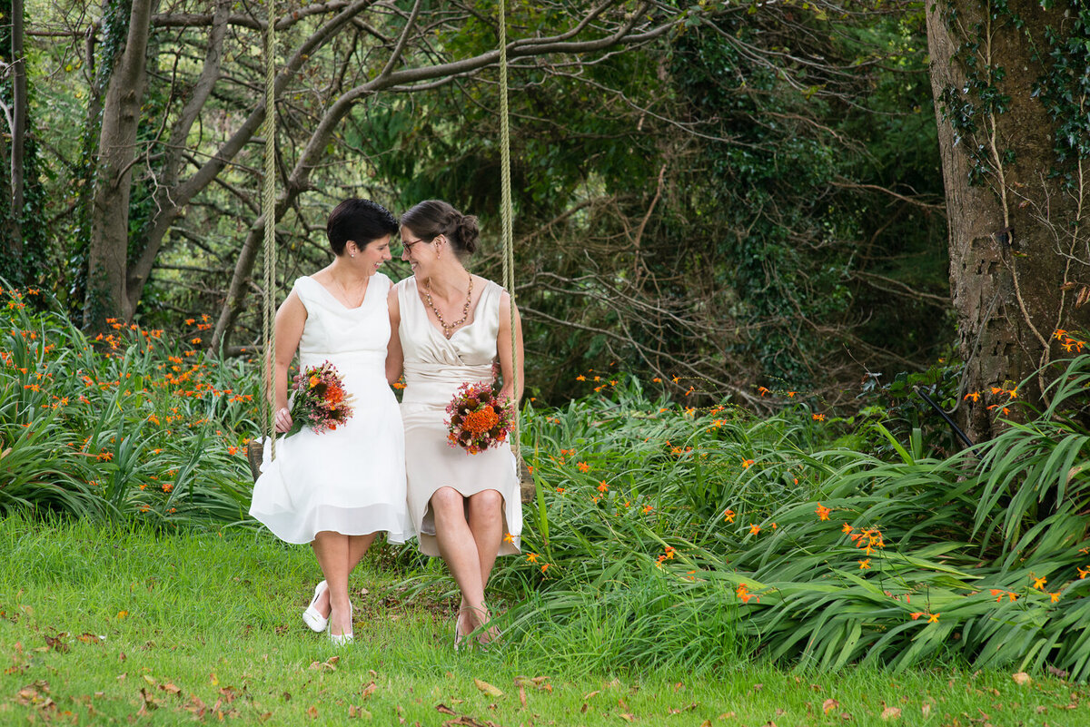 Gay wedding couple wearing white dresses, sitting on a swing, holding orange bouquets in a garden