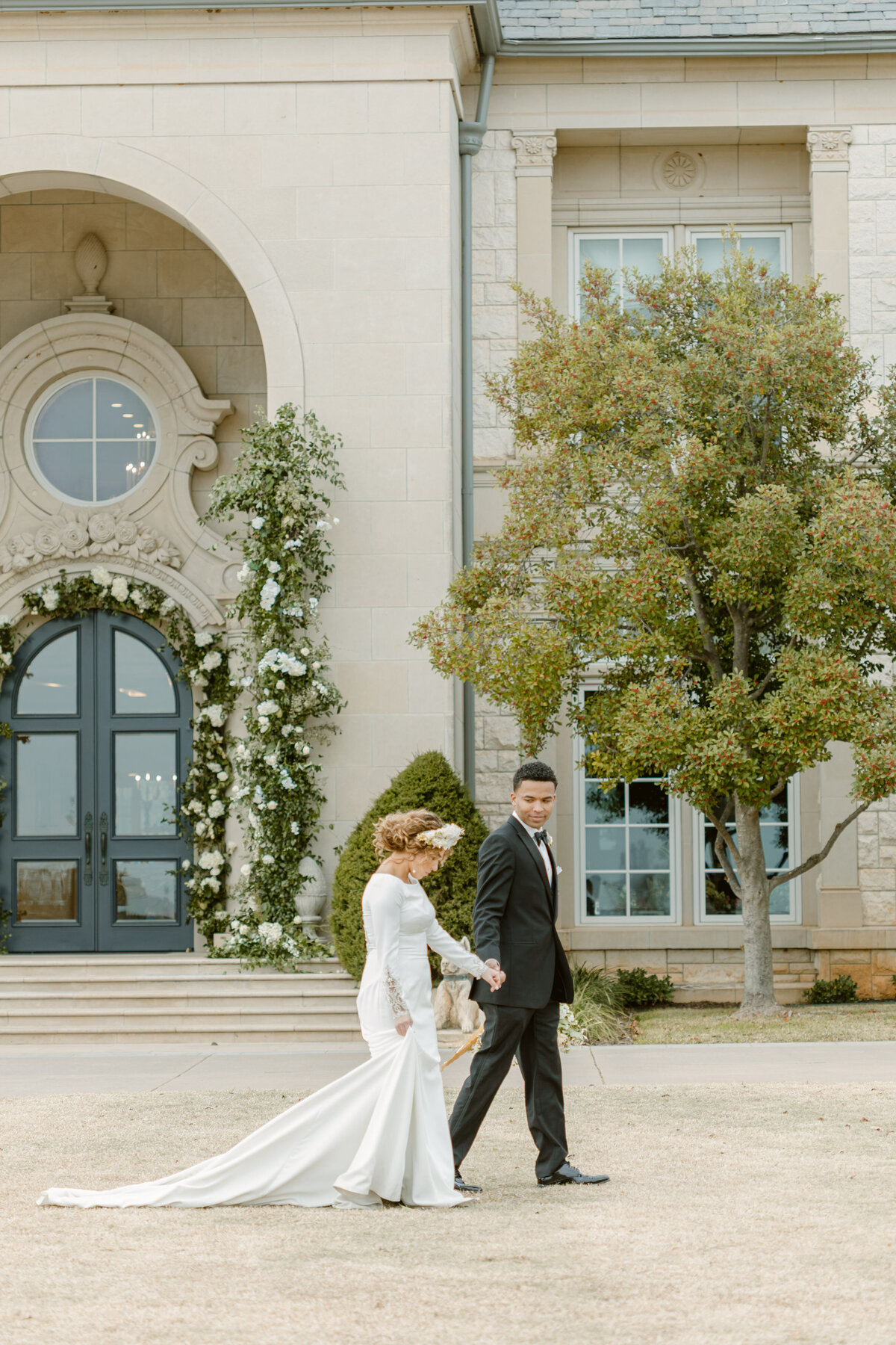 Bride and groom hold hands and walk outside their wedding venue covered in flowers