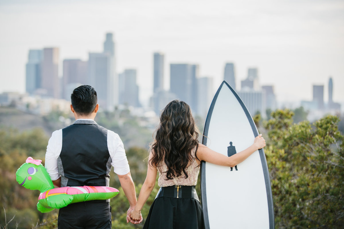 Couple holding hands looking at Los Angeles Skyline. She is holding a surfboard and he has a turtle pool float around his midsection