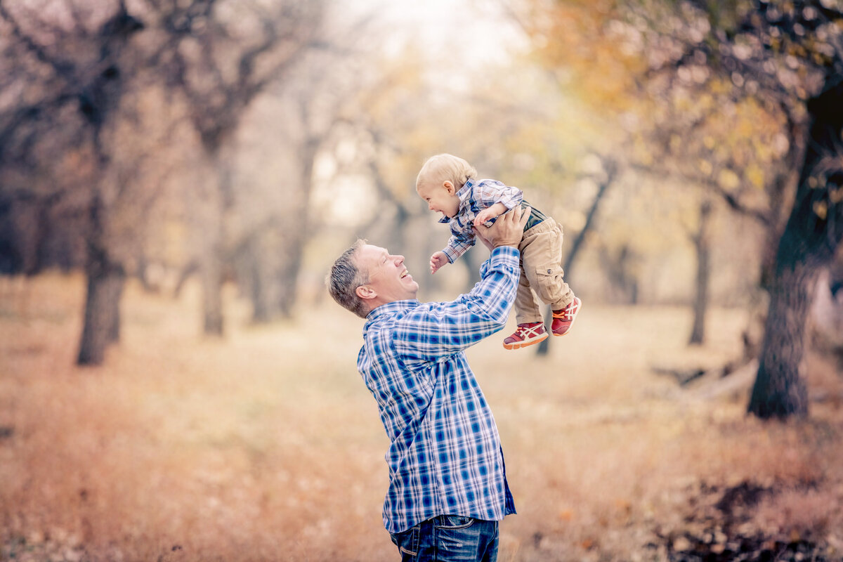 dad and son in trees by river in fall, blue plaid shirts and blue jeans, red shoes, blond and brown hair, happy family, family photographer near me.