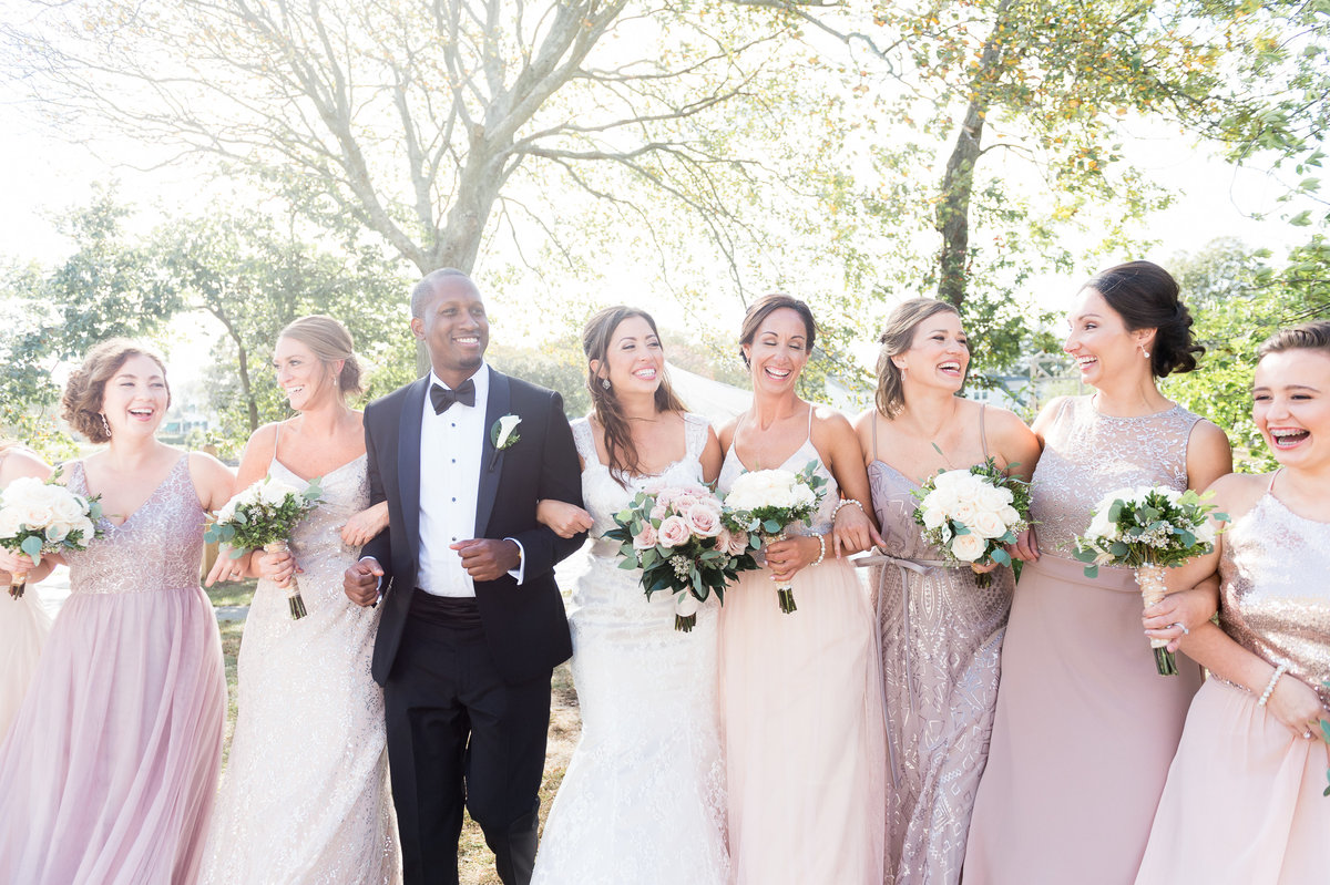 Bride, groom, and bridal party link arms holding bouquet and walk outside