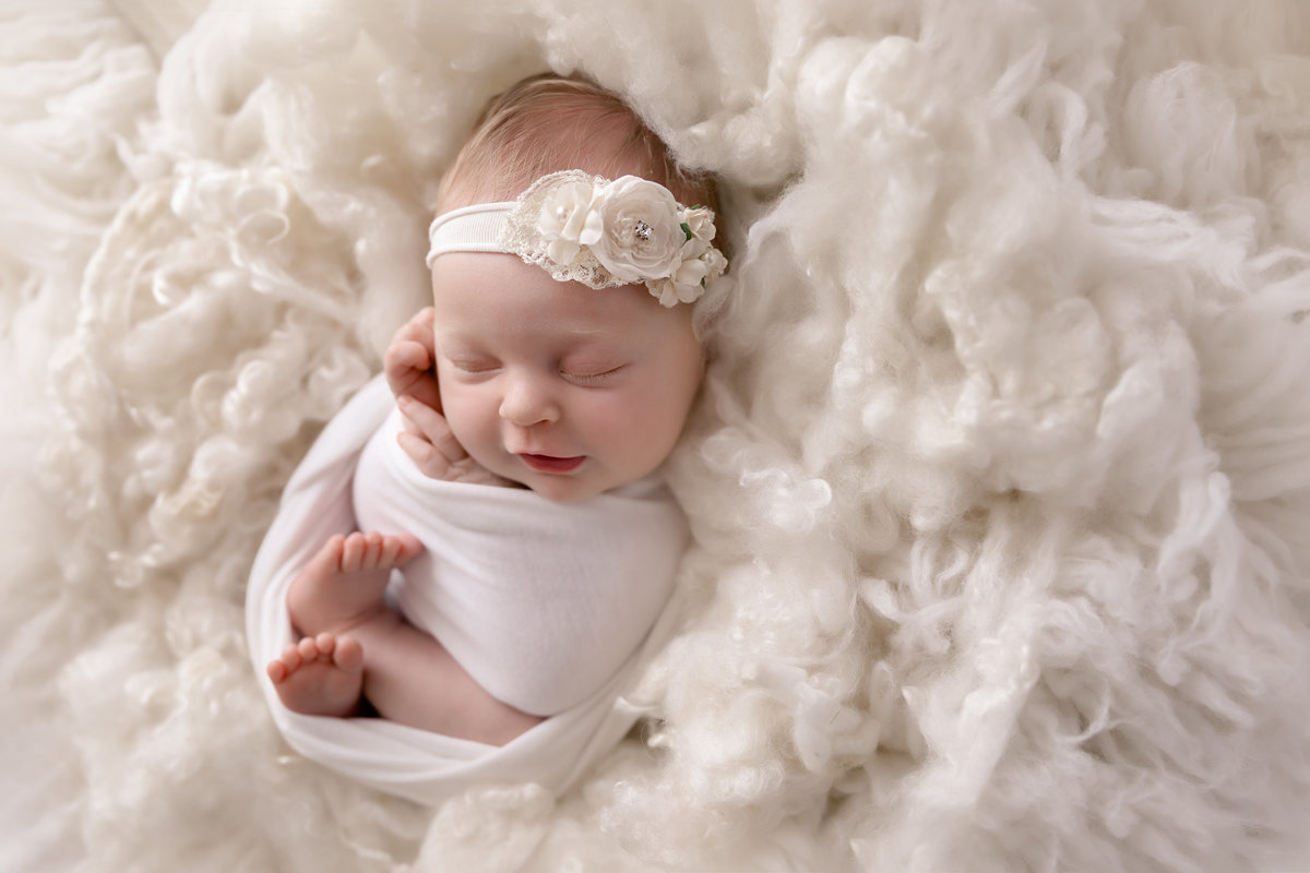 Little baby girl curled up in a white dreamy setting