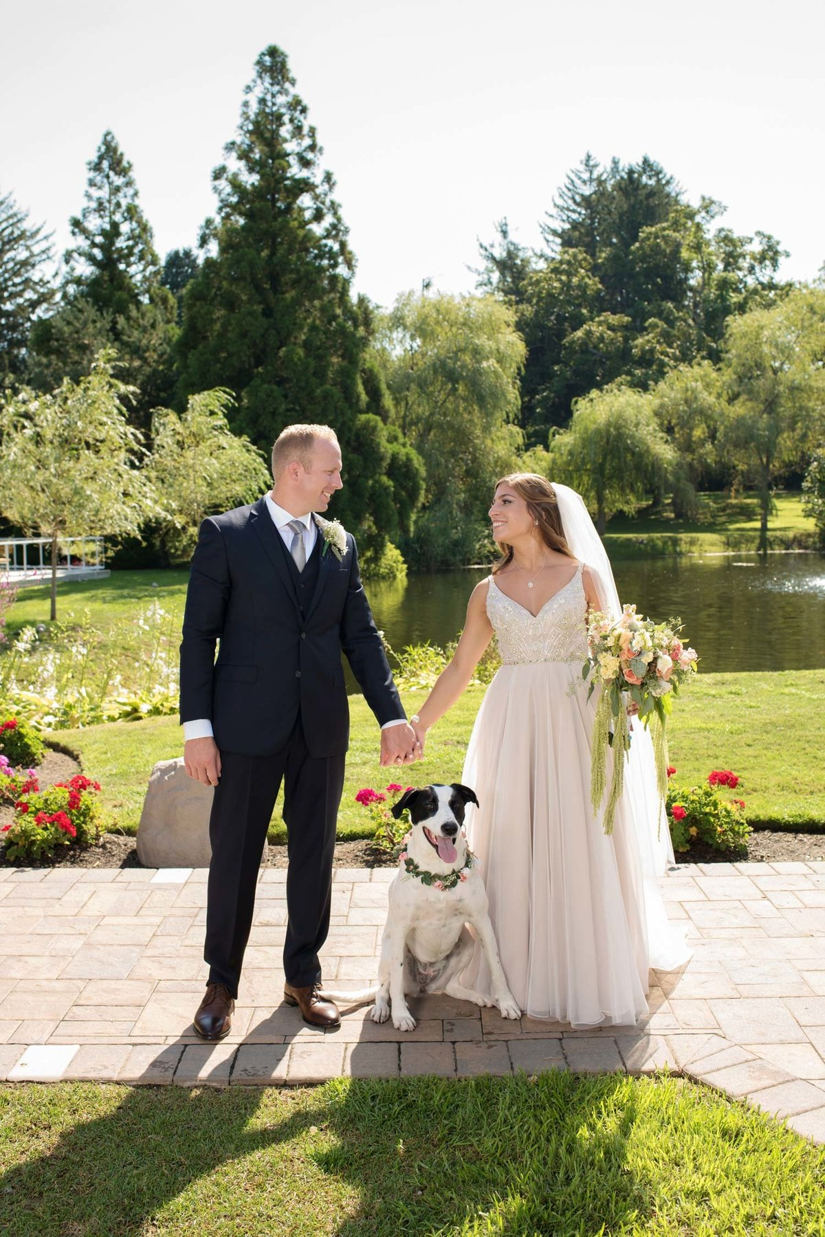 Bride and groom with their dog holding hands outside at Flowerfield
