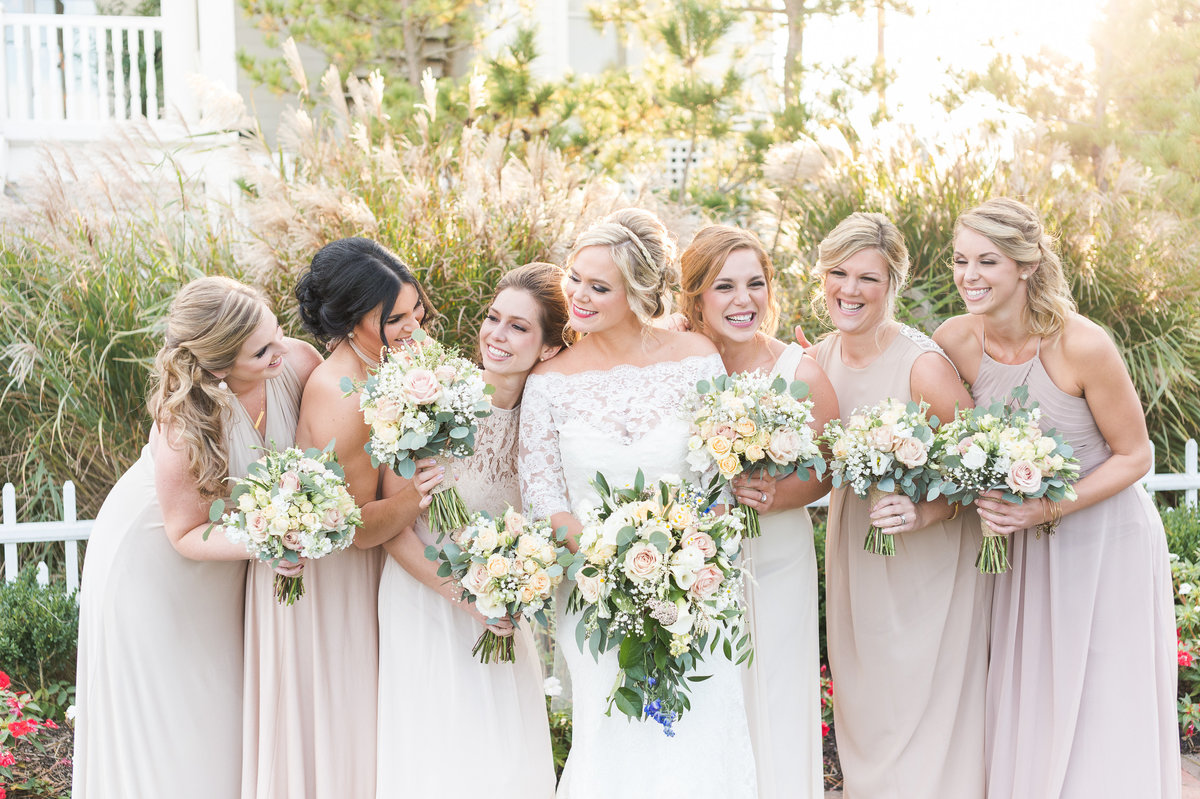 Bride and her bridal party huddle together and embrace holding bouquets