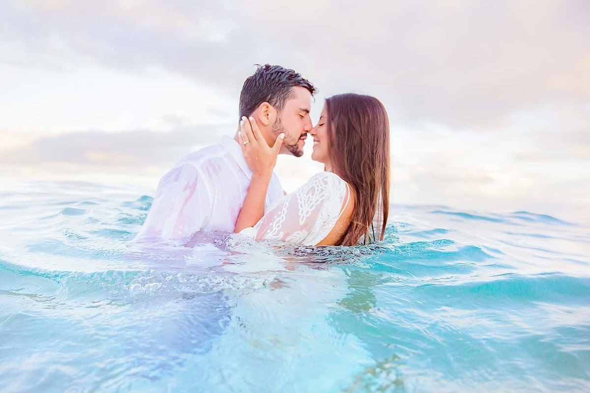 Bride and groom smiling and kissing in the water