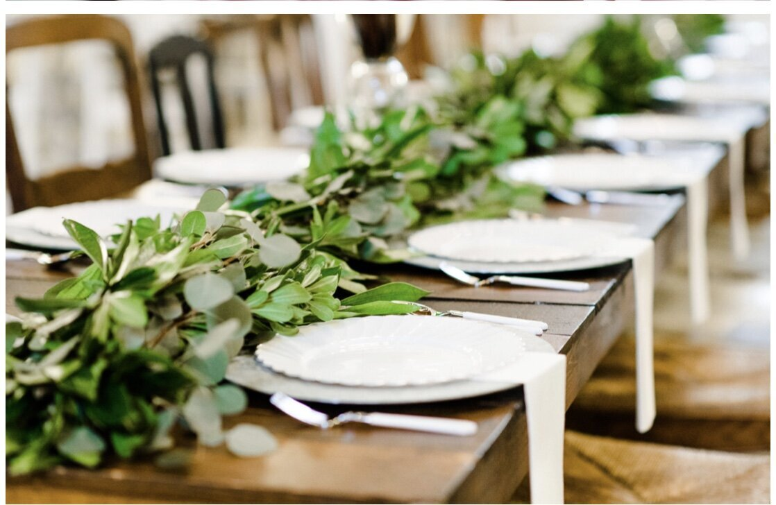 A gorgeous greenery table scape with white plates and hanging napkins