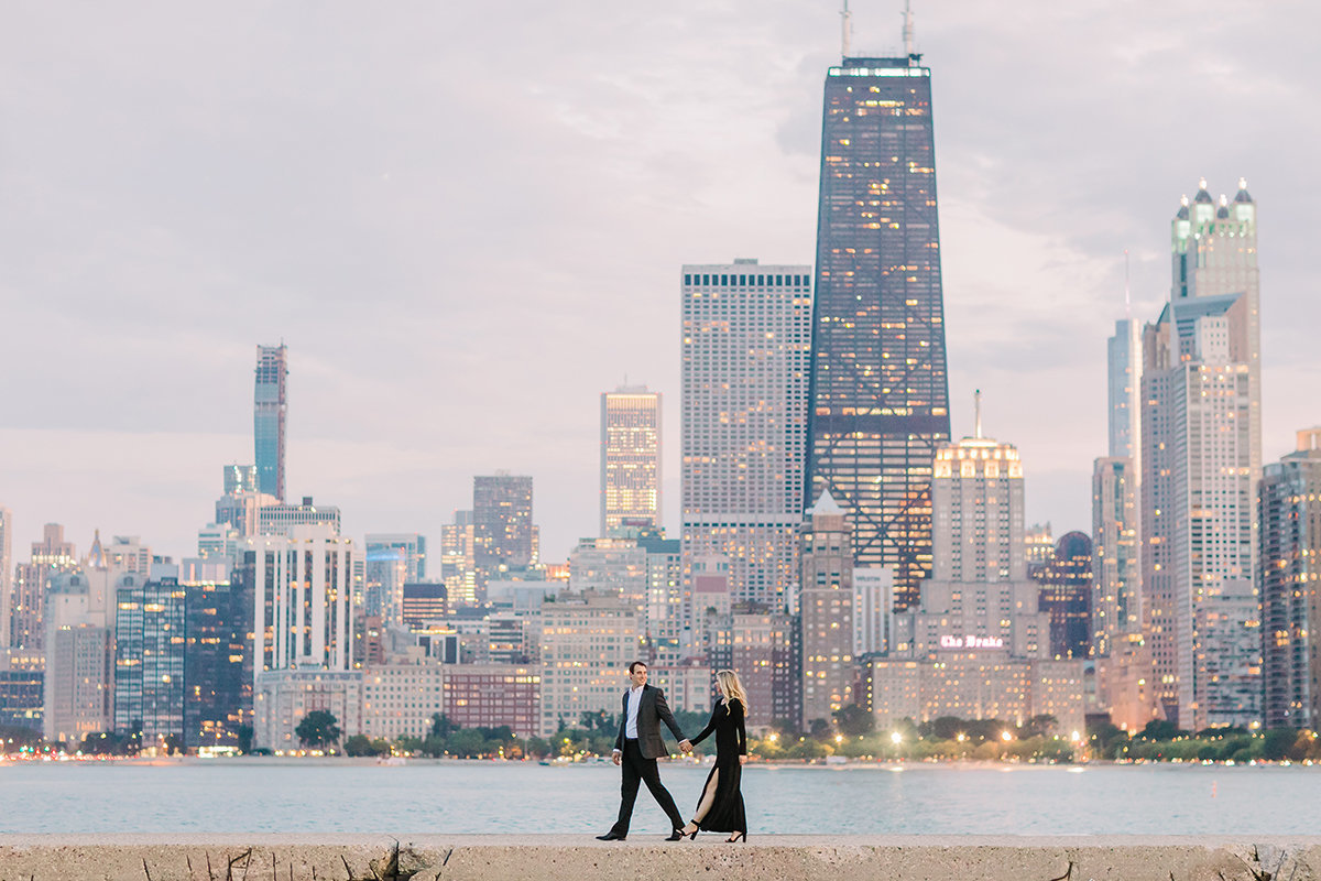 Couple hold hands and walk along the Chicago lakefront