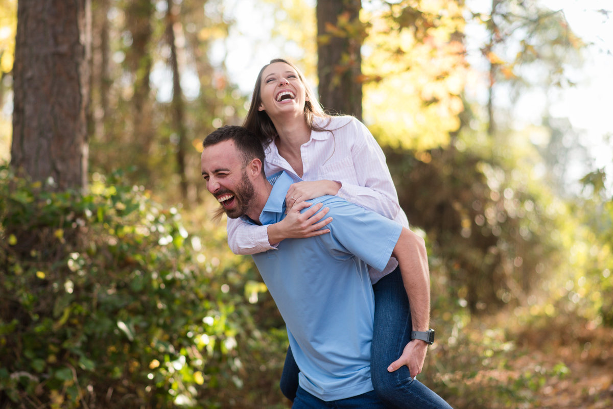 couple laughing piggy back during locks park chesapeake by virginia engagement photographer