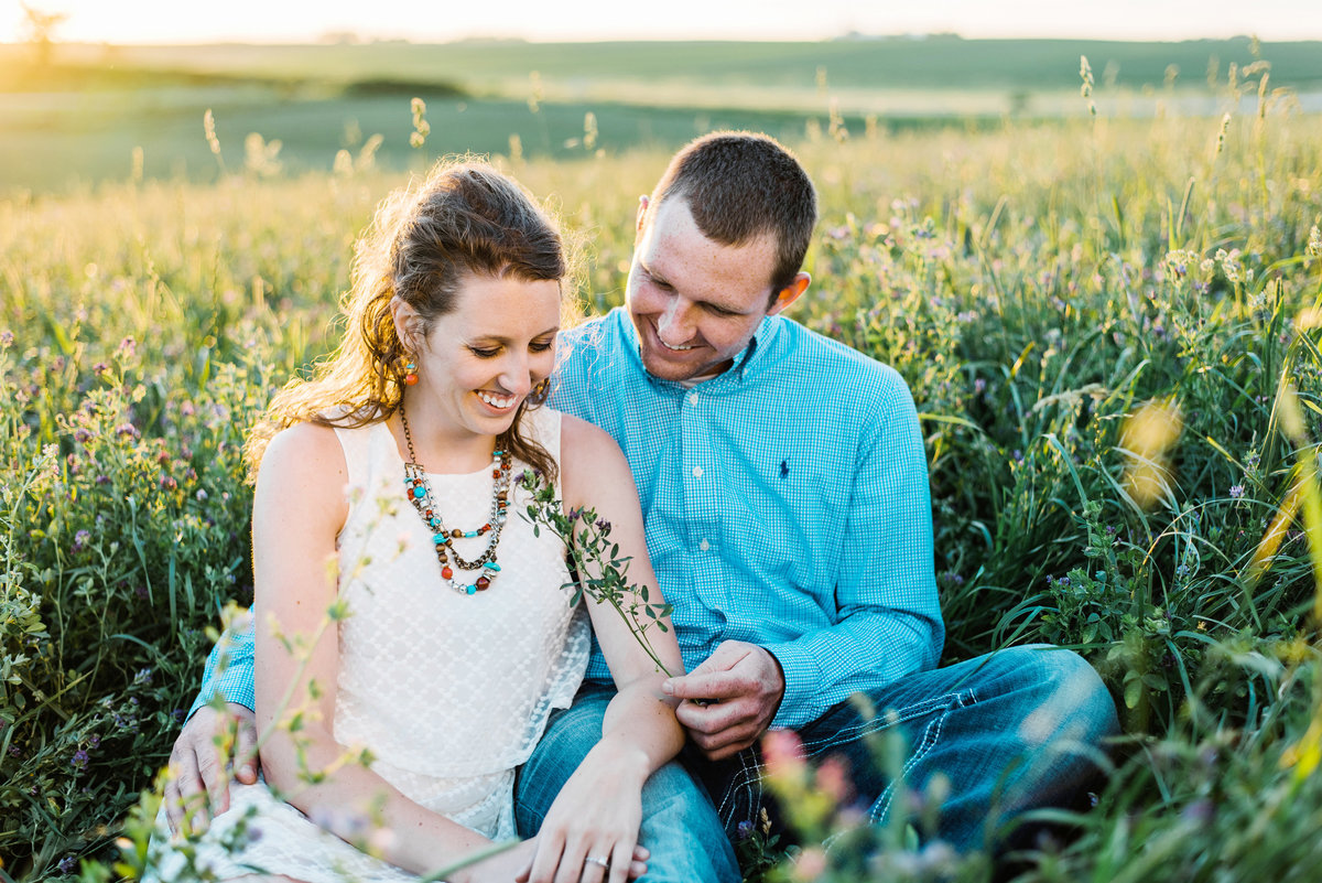 couple snuggles in an alfalfa field