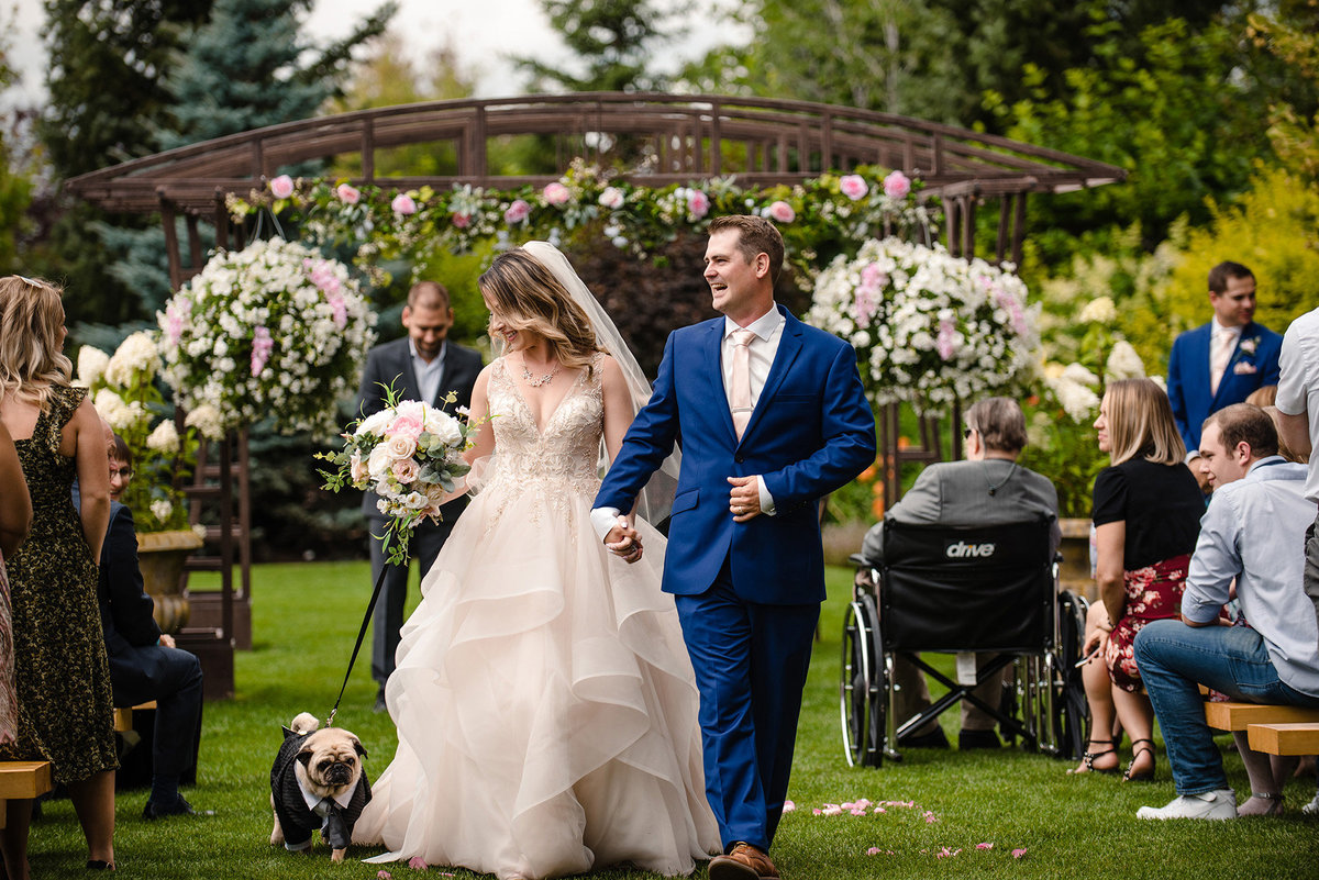 Bride and groom with a dog dressed in a tuxedo