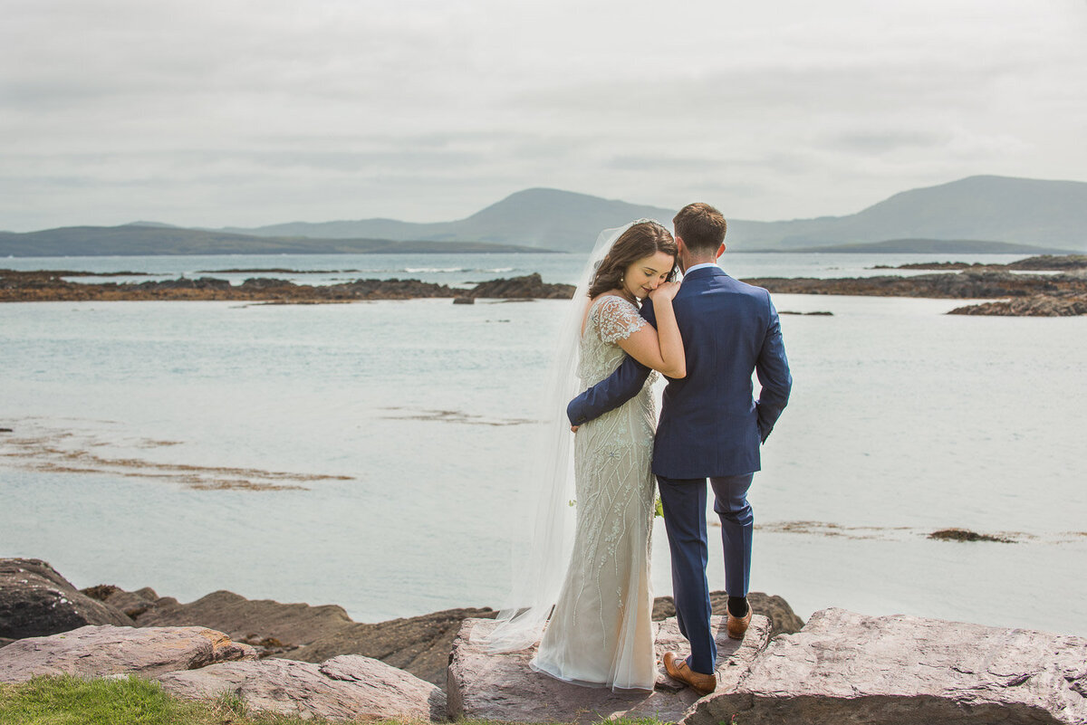 bride wearing a vintage beaded, column wedding dress hugging her husband during the first look while standing on a rock overlooking the beach in Kerry