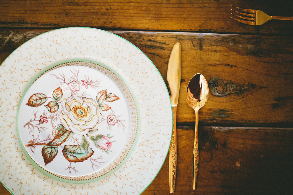 Vintage plate table setting with gold cutlery for dinner party