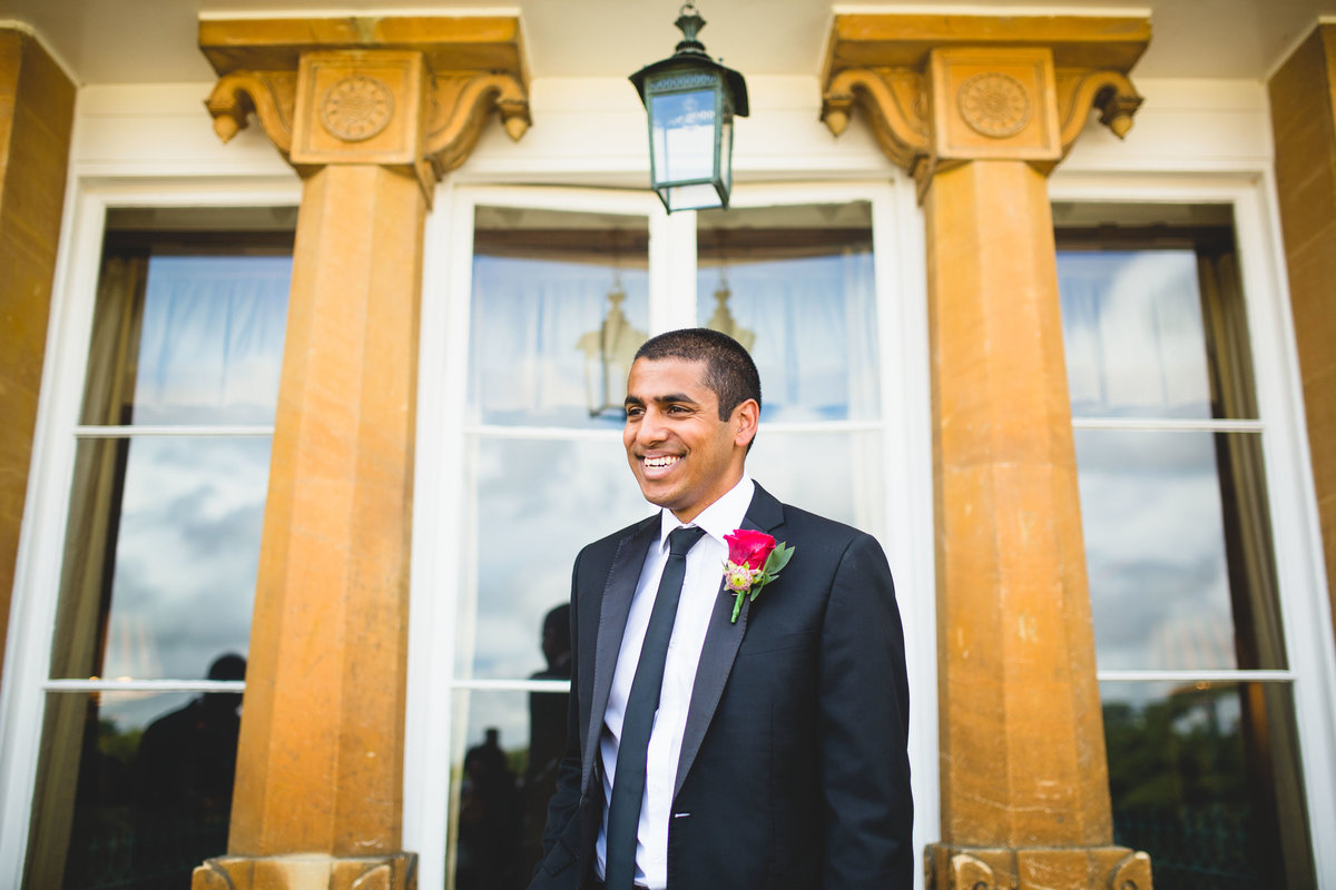 groom in black suit laughing at this sezincote house wedding in gloucestershire