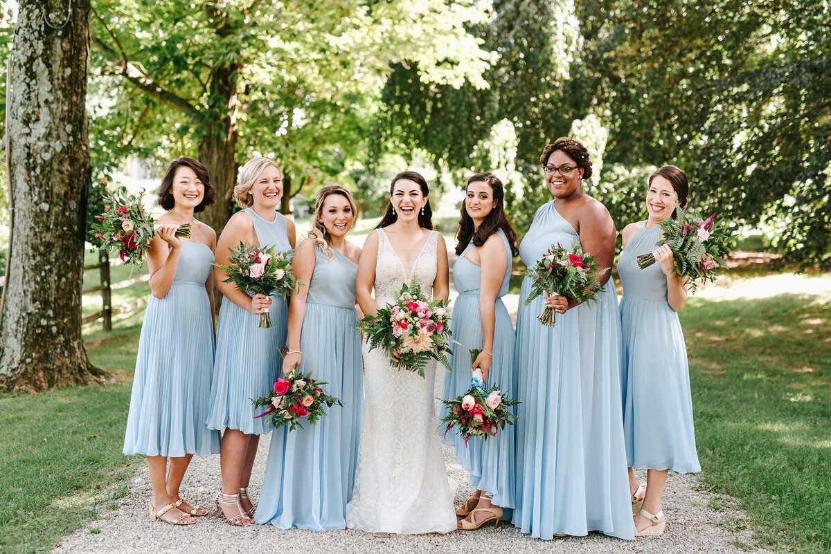 Bridal party smiles with their bride outside holding bouquets