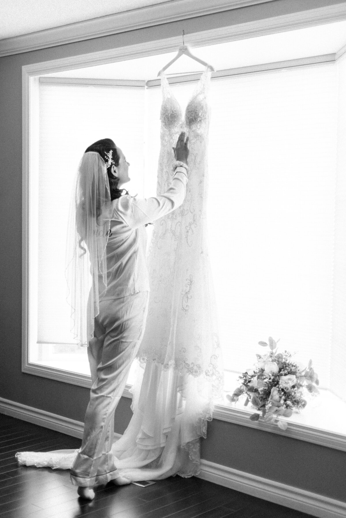 A bride looks at the detail on her lace dress before getting dressed