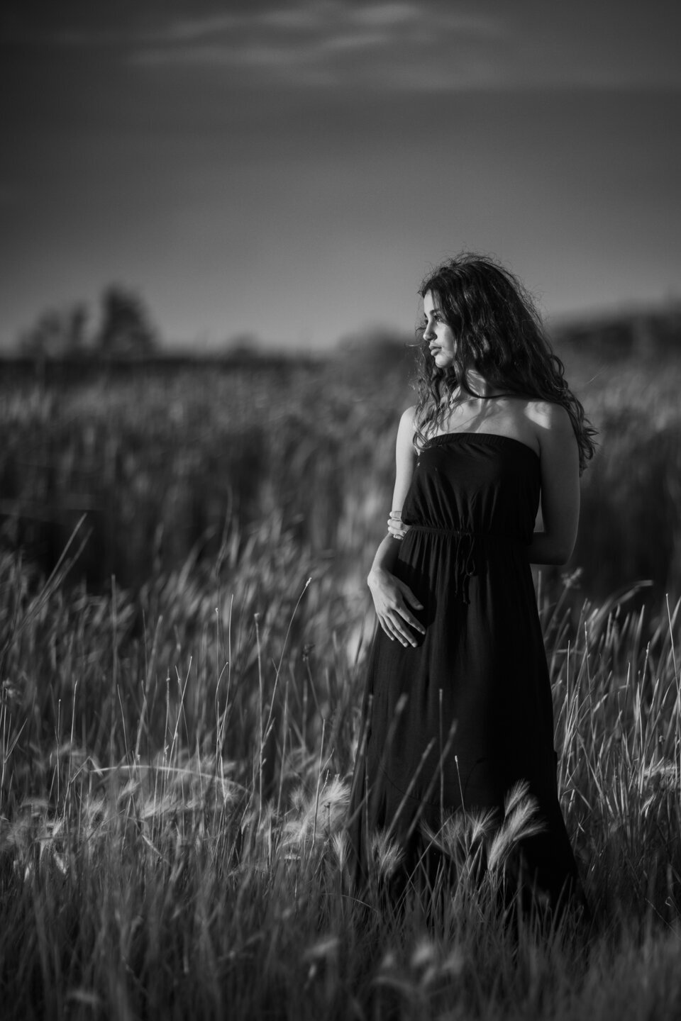 girl in black dress with long dark hair  looking towards the sunset, pictures taken at joels pond in billings montana, in cattails next to the pond.