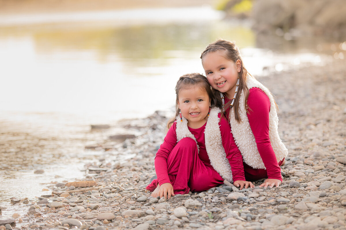 Pictures of sisters sitting next to the Yellowstone River at sunset.