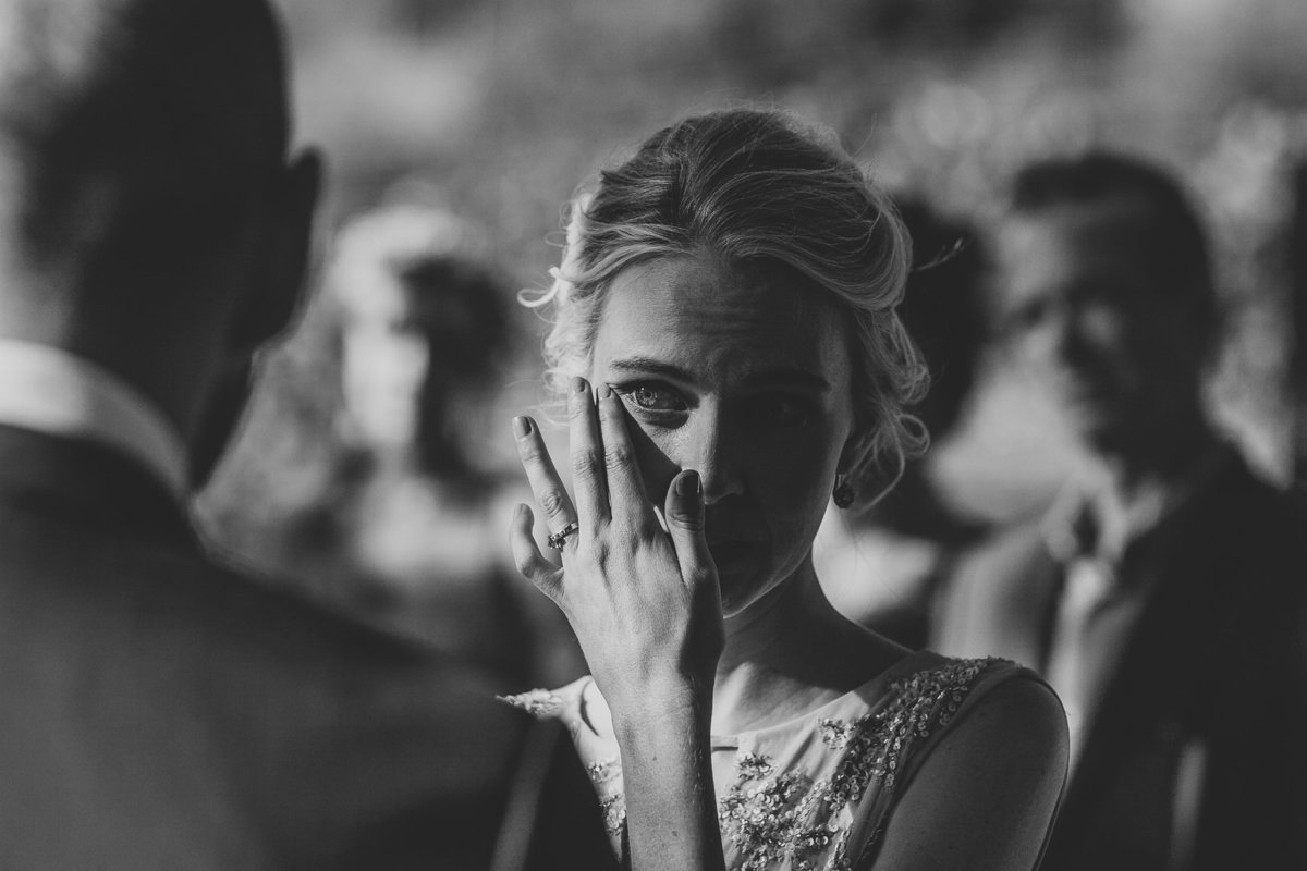 Bride wipes a tear of joy during her wedding ceremony in Malibu, Ca.