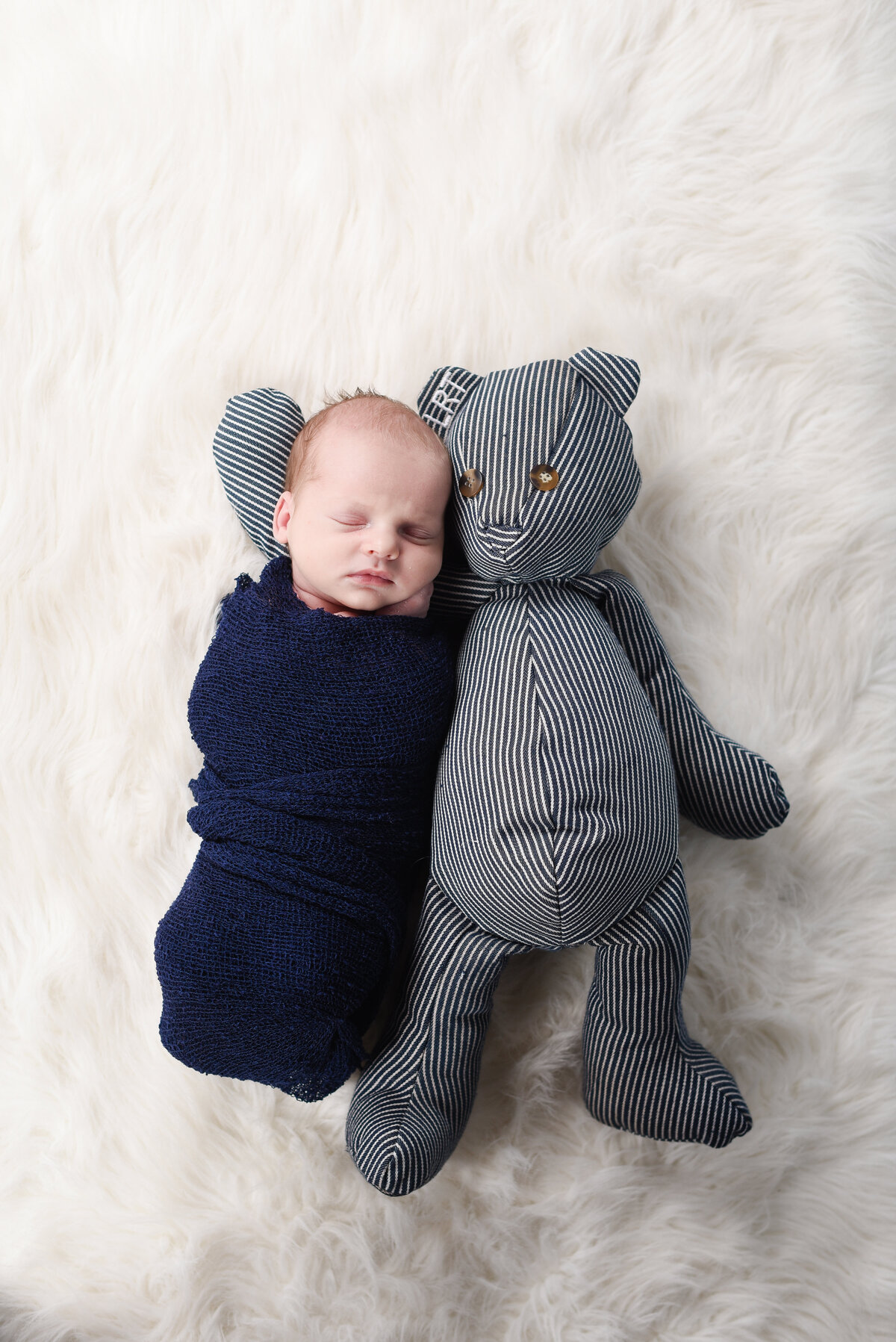 Beautiful Mississippi newborn photography: newborn boy with a teddy bear made from his grandfather's overalls in Mississippi