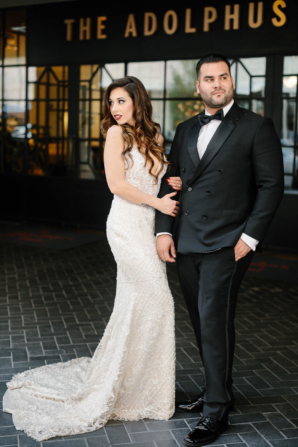 bride and groom standing outside Adolphus hotel entrance