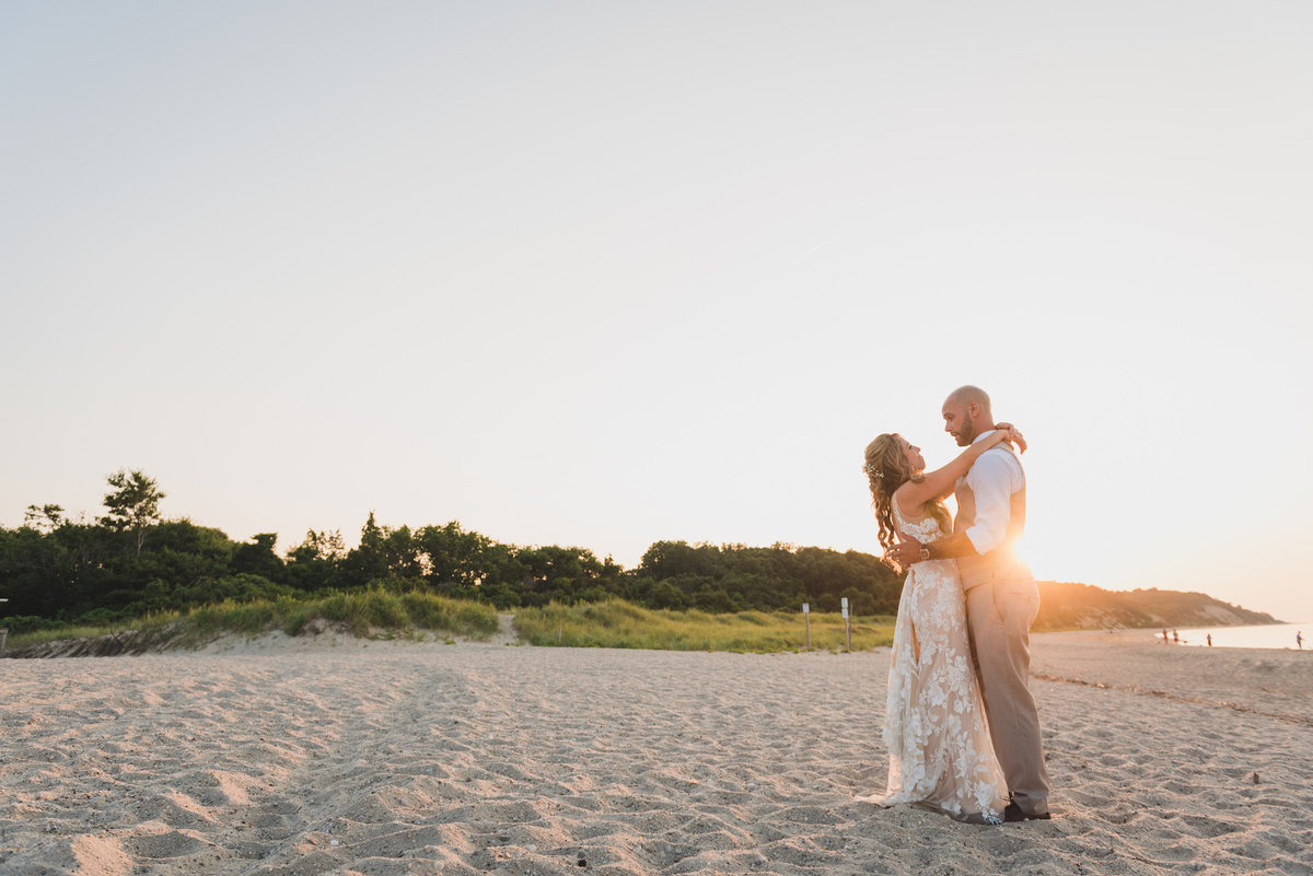 photo of bride and groom on the beach with sunsetting behind them from wedding at Pavilion at Sunken Meadow