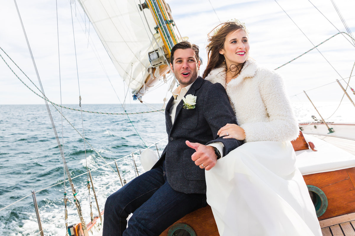 The bride and groom relish in the wind aboard the Silverlining Sailing boat at their Ogunquit Maine elopement