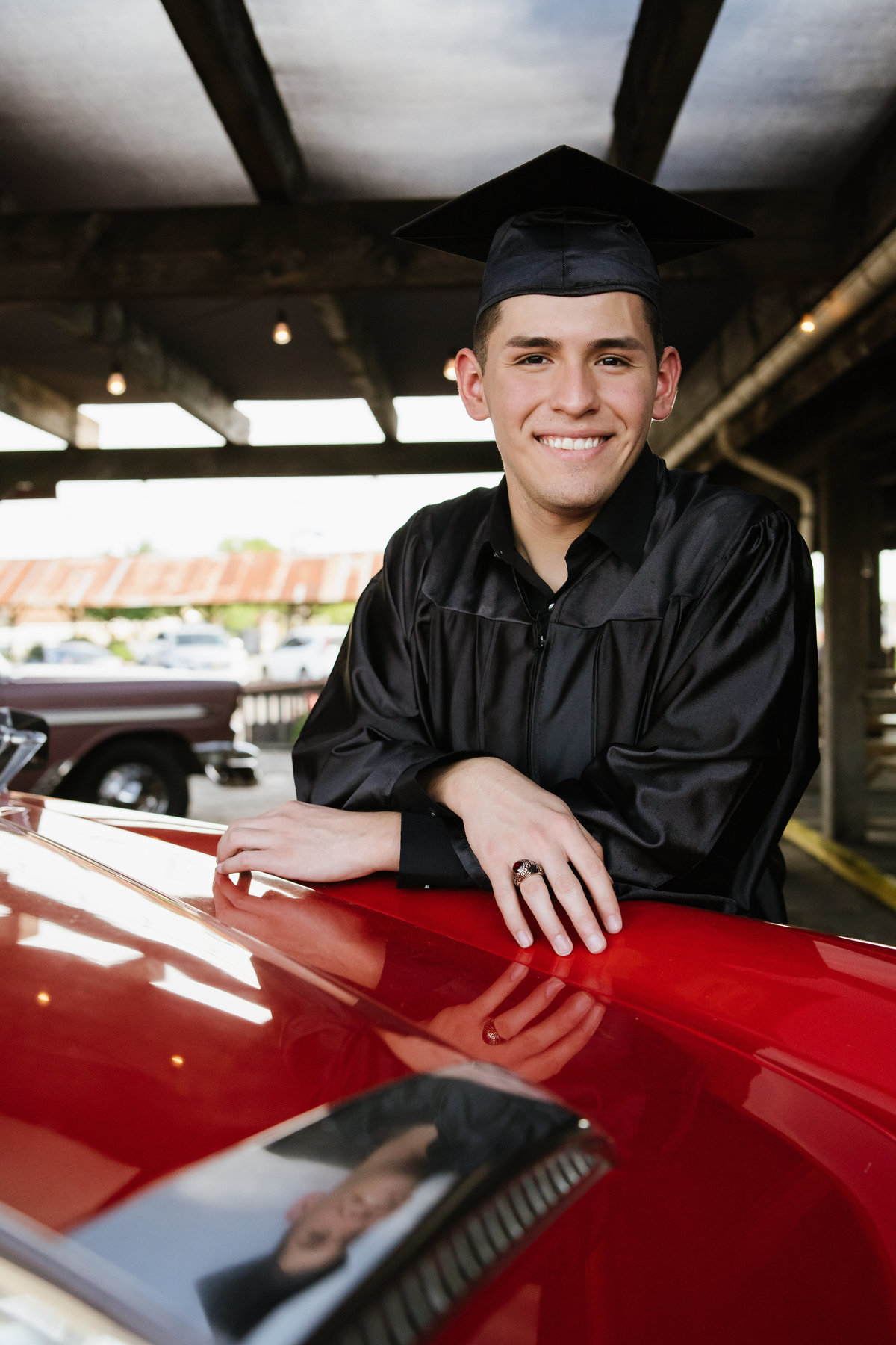 high school senior cap  and gown posing by classic car by San Antonio senior photographer