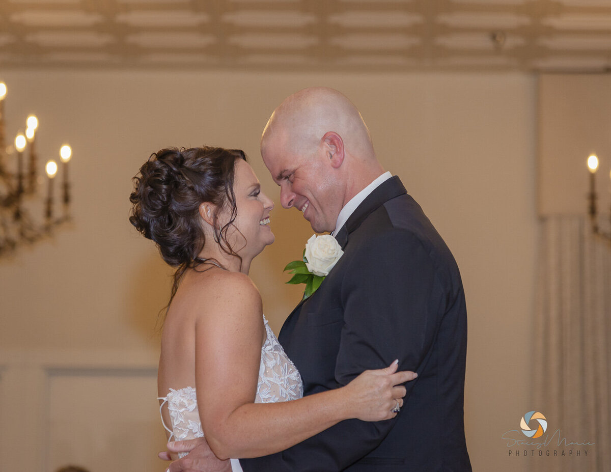 Couple smile and look into each others eyes as they have their first dance.