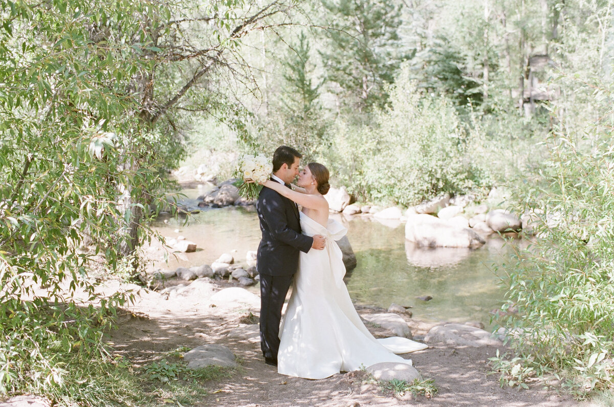 Bride and groom kissing under trees near a slow river