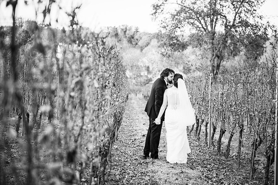 Bride and groom kiss in the vineyards of Galer Estate Winery