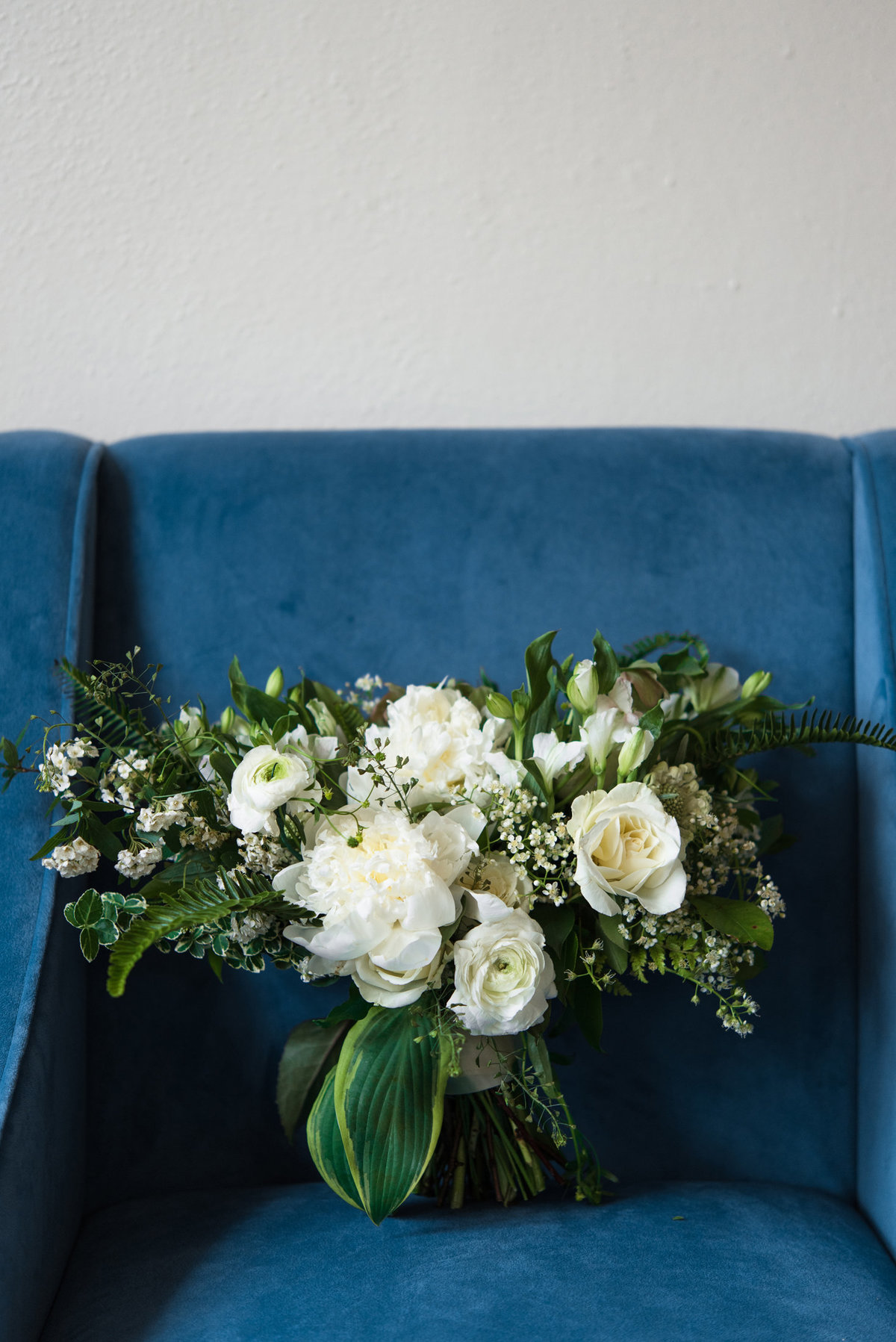 blue velvet chair and everbloom designs bouquet