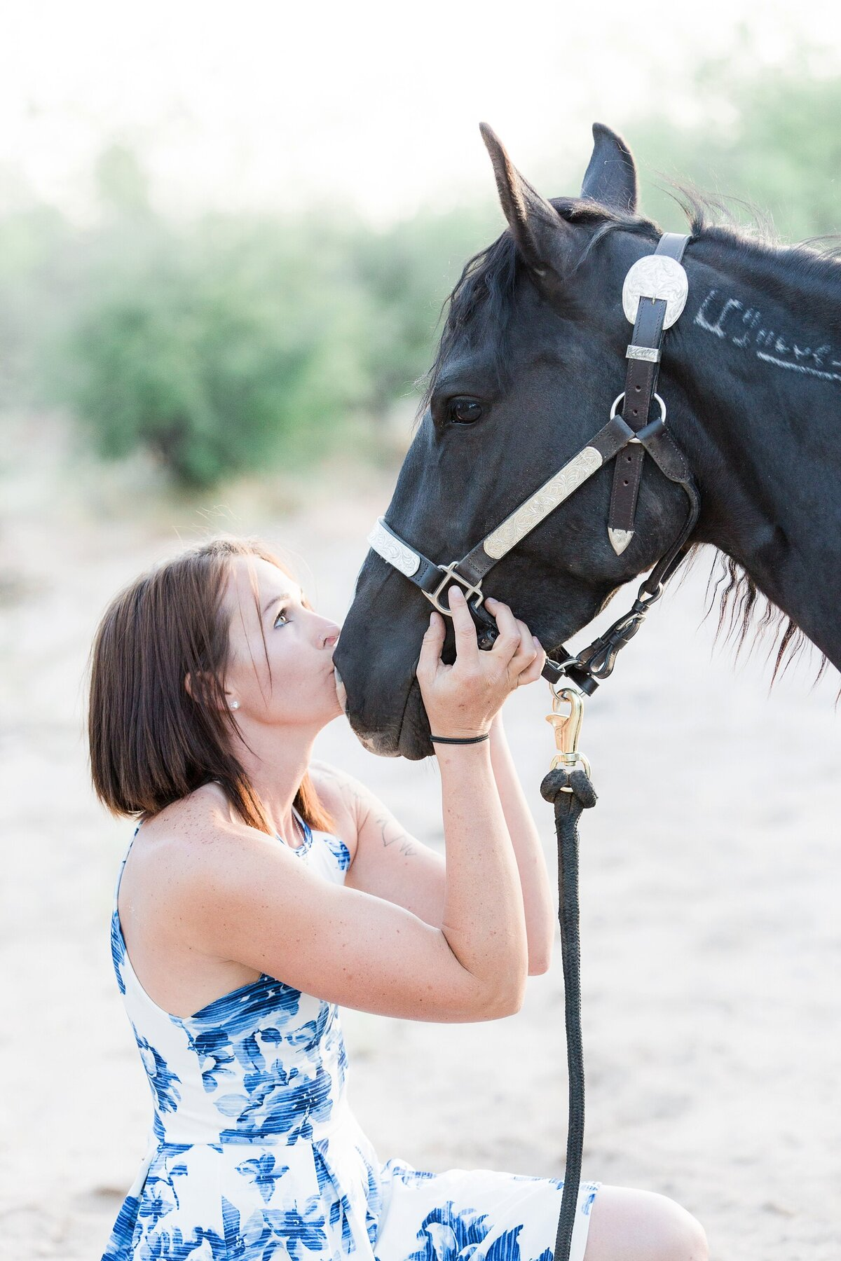 girl kissing her black mustang on the nose
