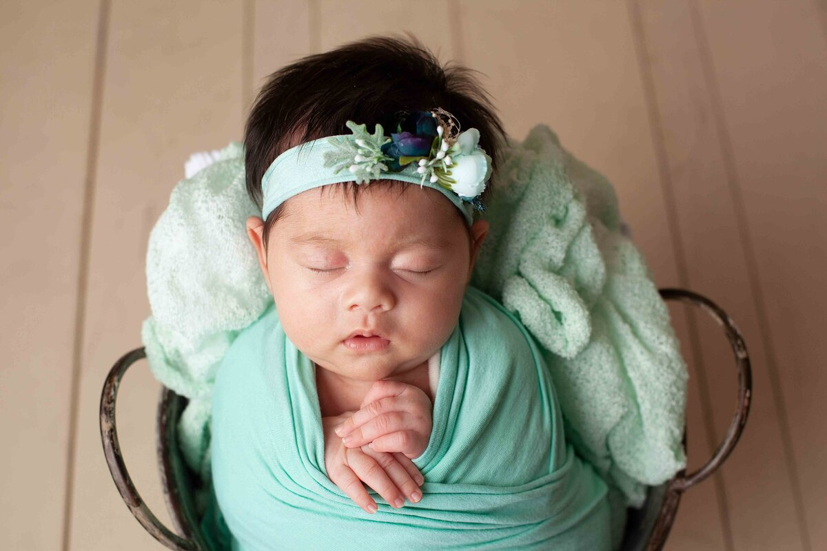 newborn girl in teal wrap and headband in a prop bucket