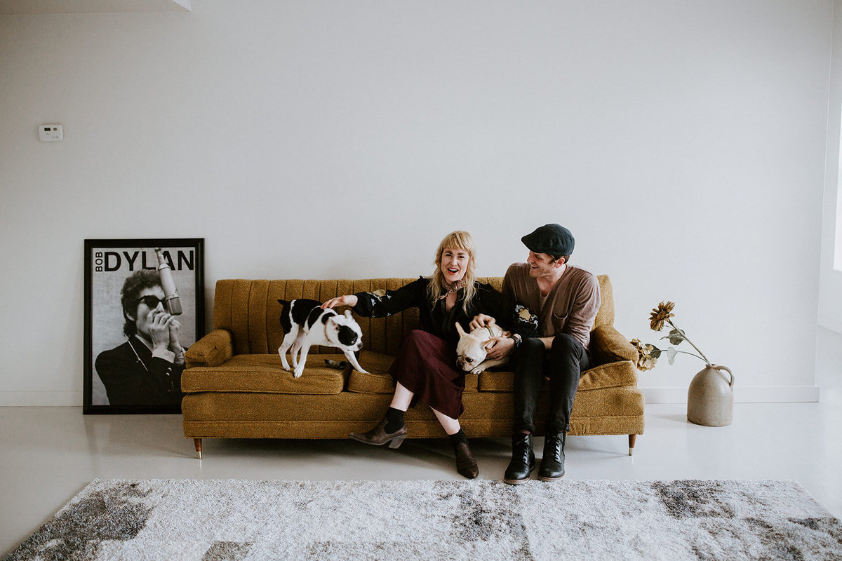 A couple sit on their couch with pets.