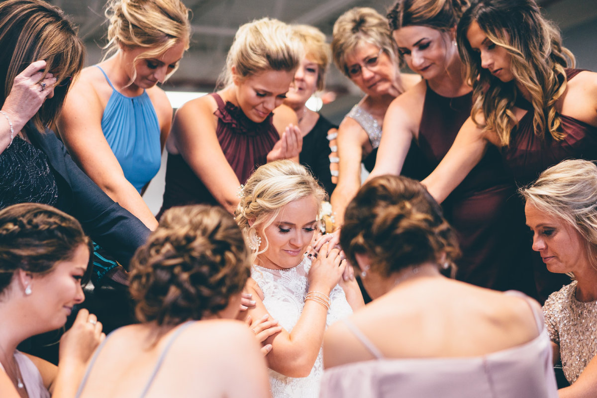 Bridemaids and mother praying for the Bride
