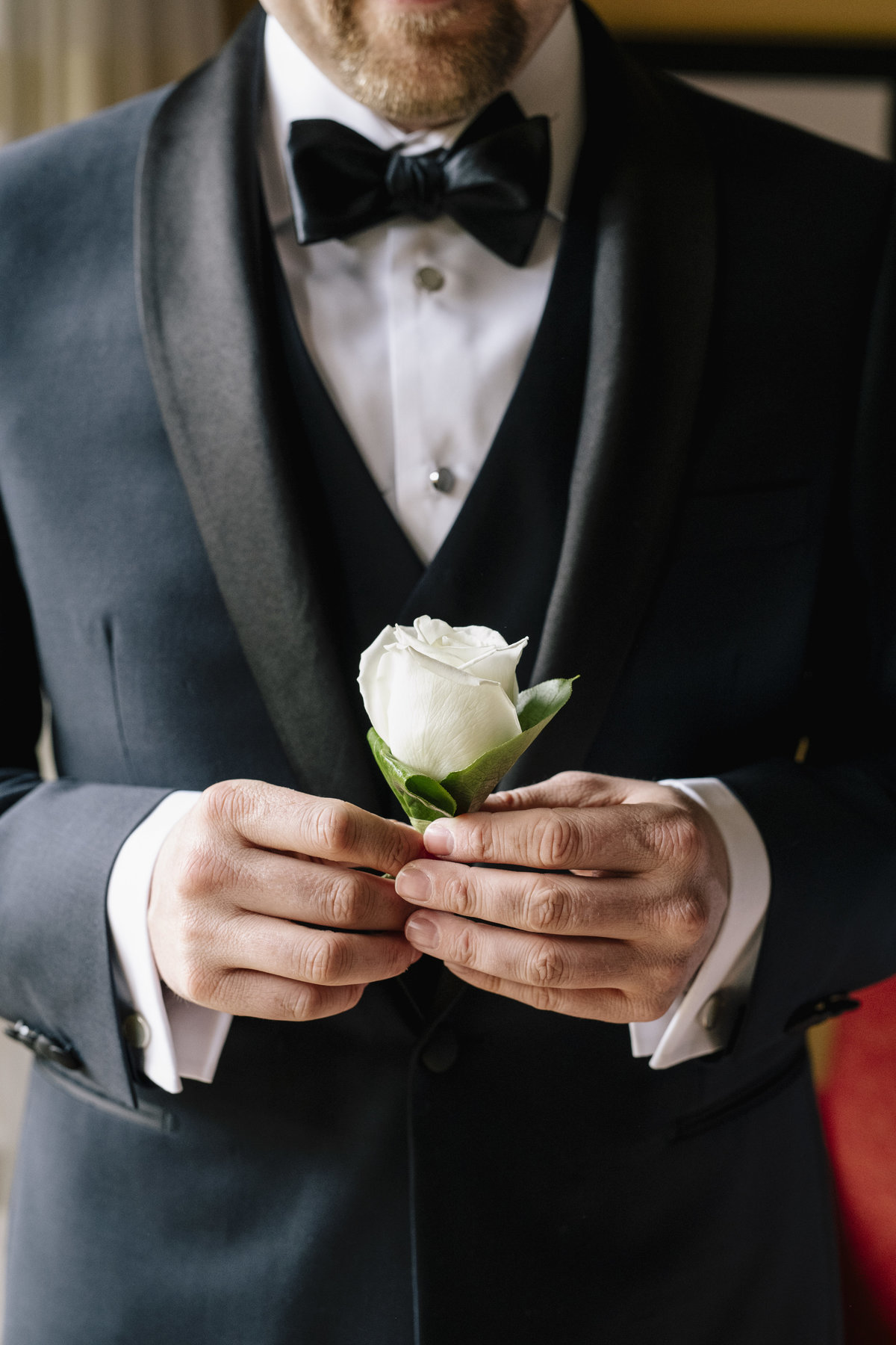groom holding his boutonniere before wedding