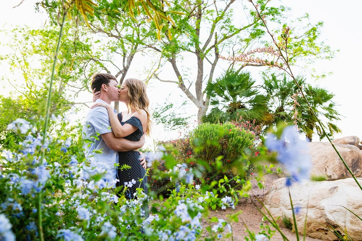 Couple kissing in a garden at their Anthem Park engagement session by Phoenix engagement photographer PMA Photography.