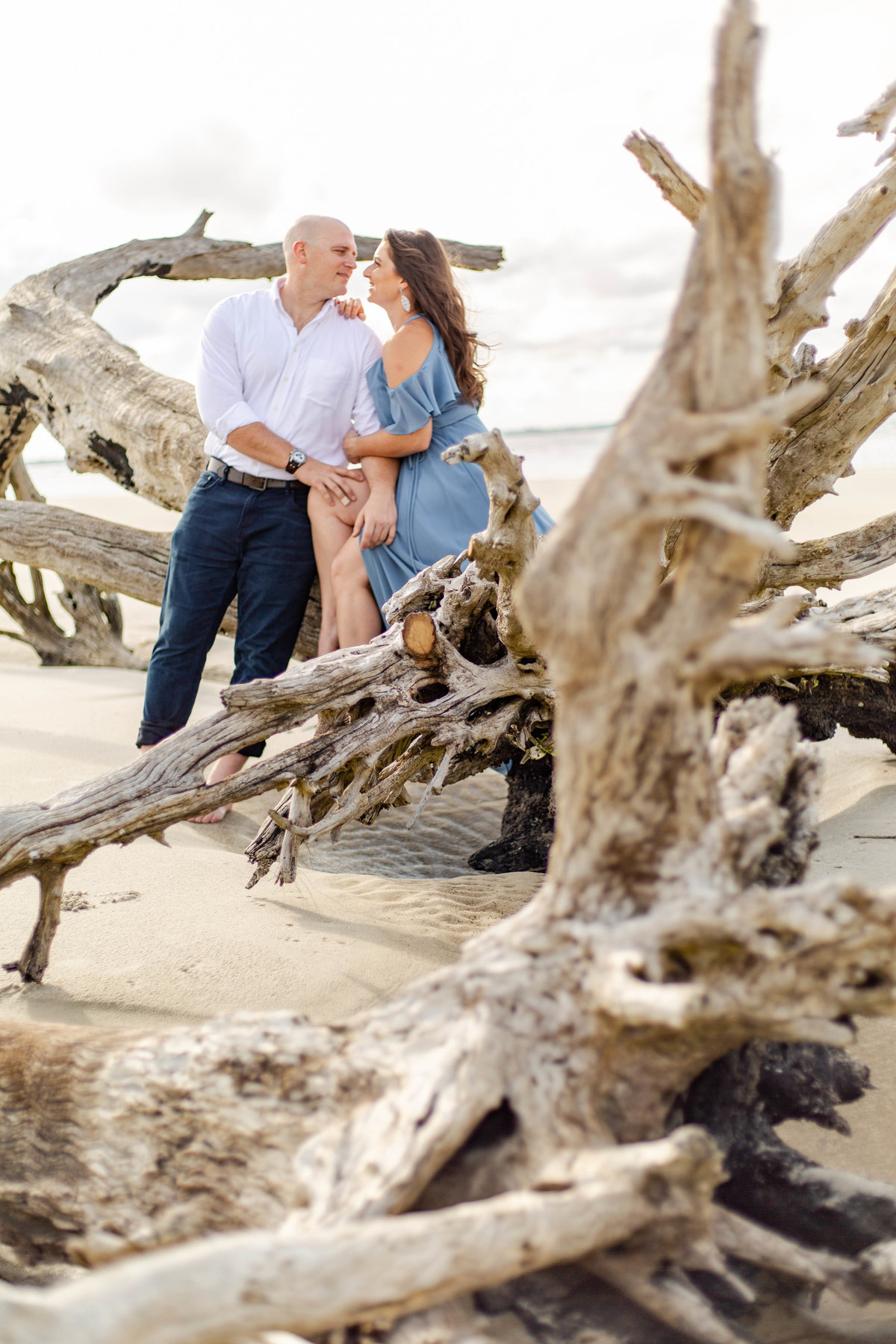 Couple looks at each other on beach in Jekyll Island in Georgia for their destination engagement photos