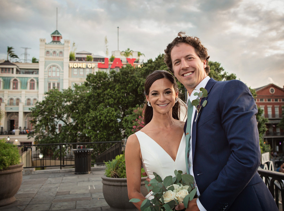 NOLA destination wedding couple with JAX Brewery in the backgroound