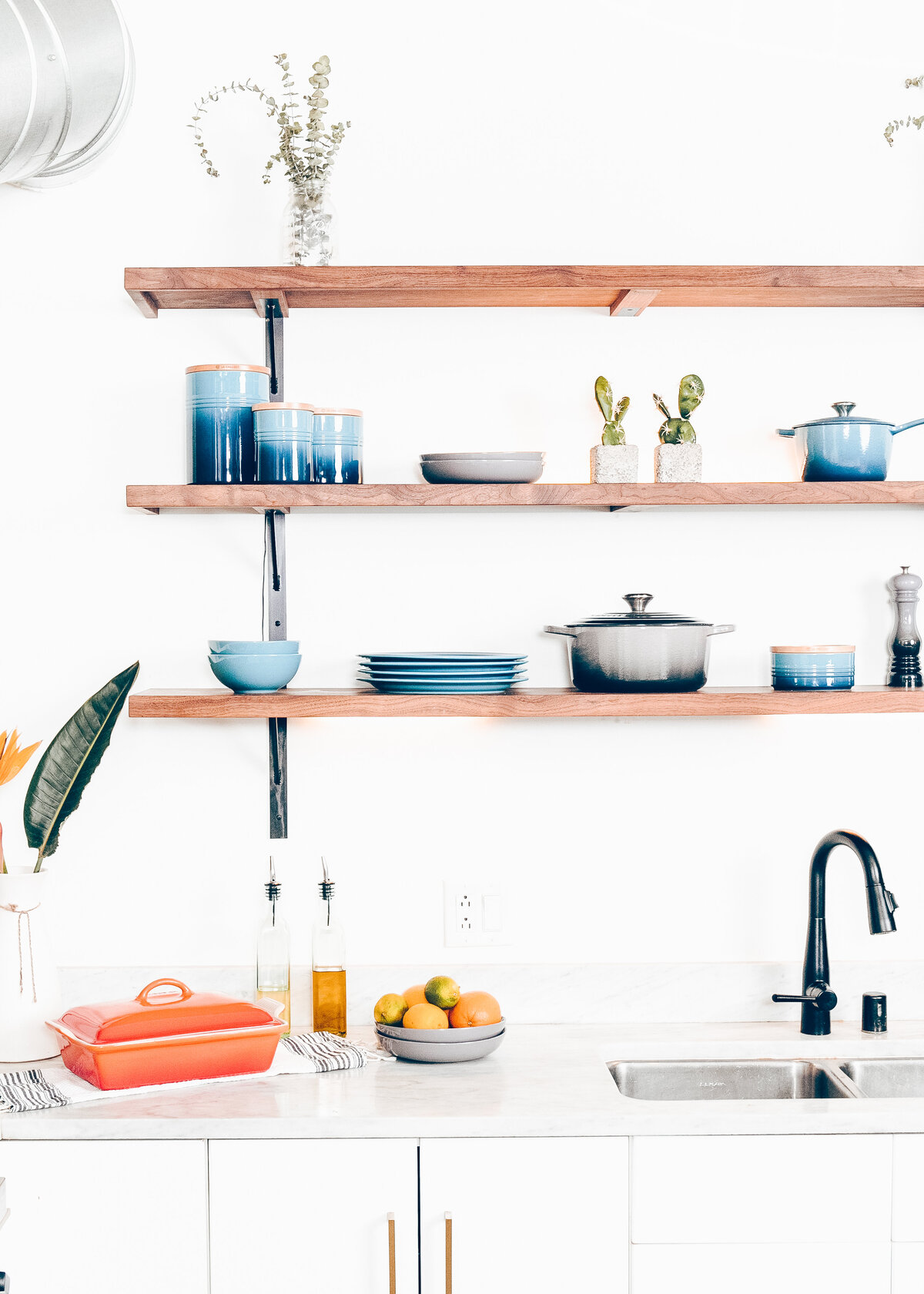 A white kitchen is accented with wooden shelves filled with blue ceramic pots and an orange casserole dish.