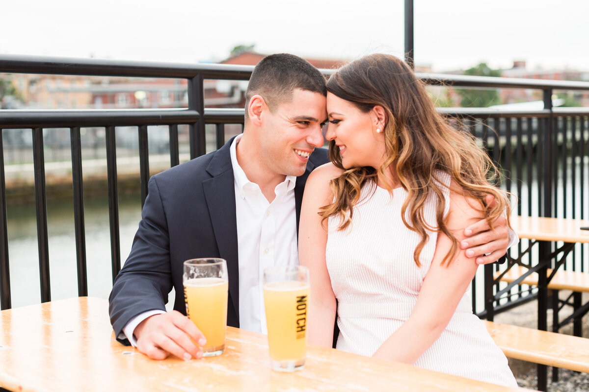 couple touching foreheads and drinking beer at brewery in Boston