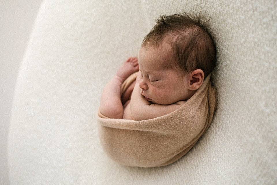 Baby girl curled during newborn session on a white blanekt