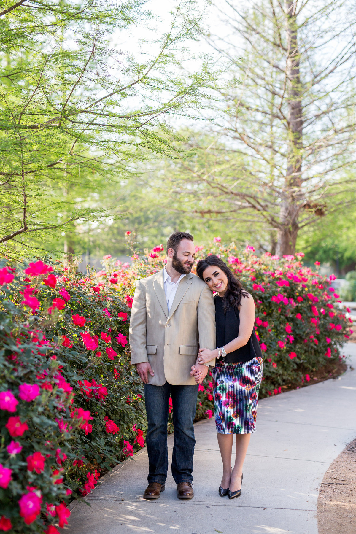 Engagement photography session of woman putting her head on the shoulder of her fiancé standing next to roses and the San Antonio Riverwalk.