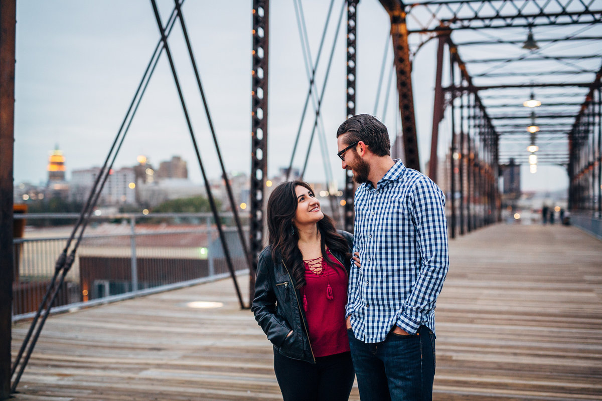 Winter engagement session in downtown San Antonio at the Hays Street Bridge. Fiancée in jacket and Fiancé in flannel shirt.