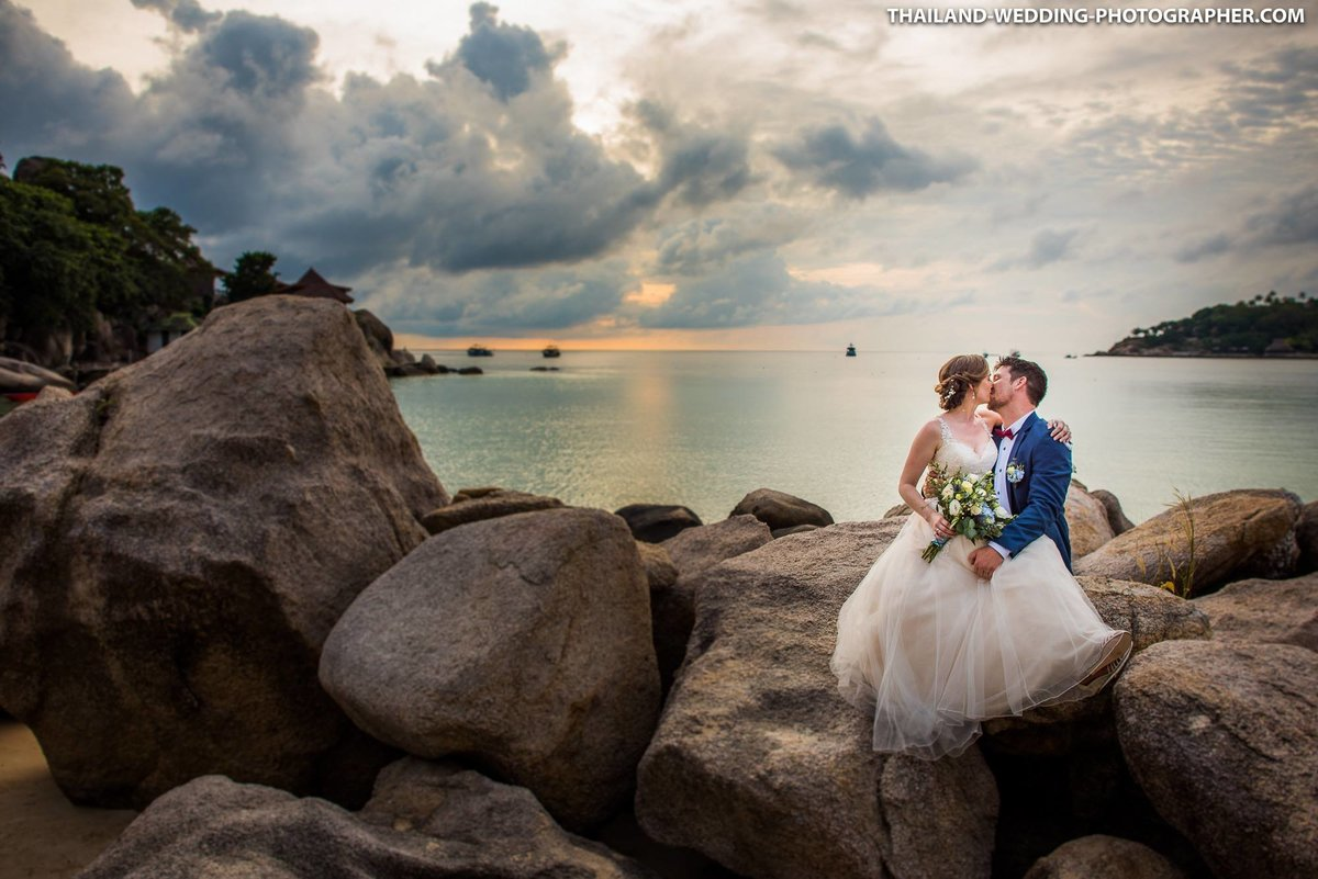 Bride and Groom sitting on rocks at Freedom Beach