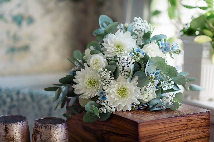 White, green and blue wedding bouquet lies on wooden box in historic room