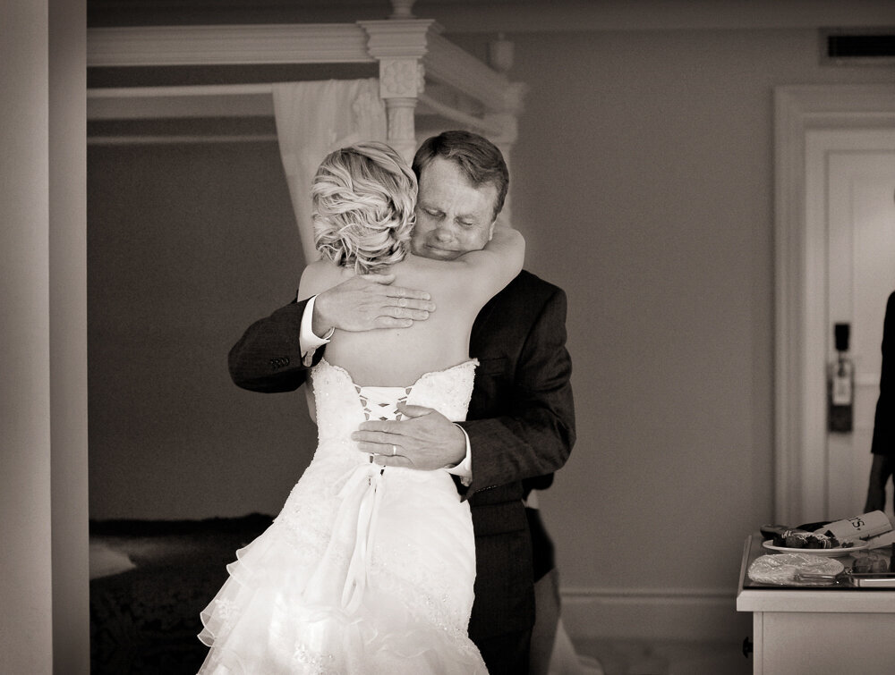 Father of the bride hugging his daughter who is wearing a corset style wedding dress in the bridal suite of the Muckross Park Hotel