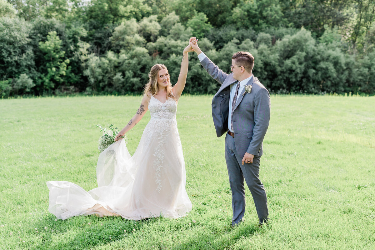 newly wed couple dancing in a field