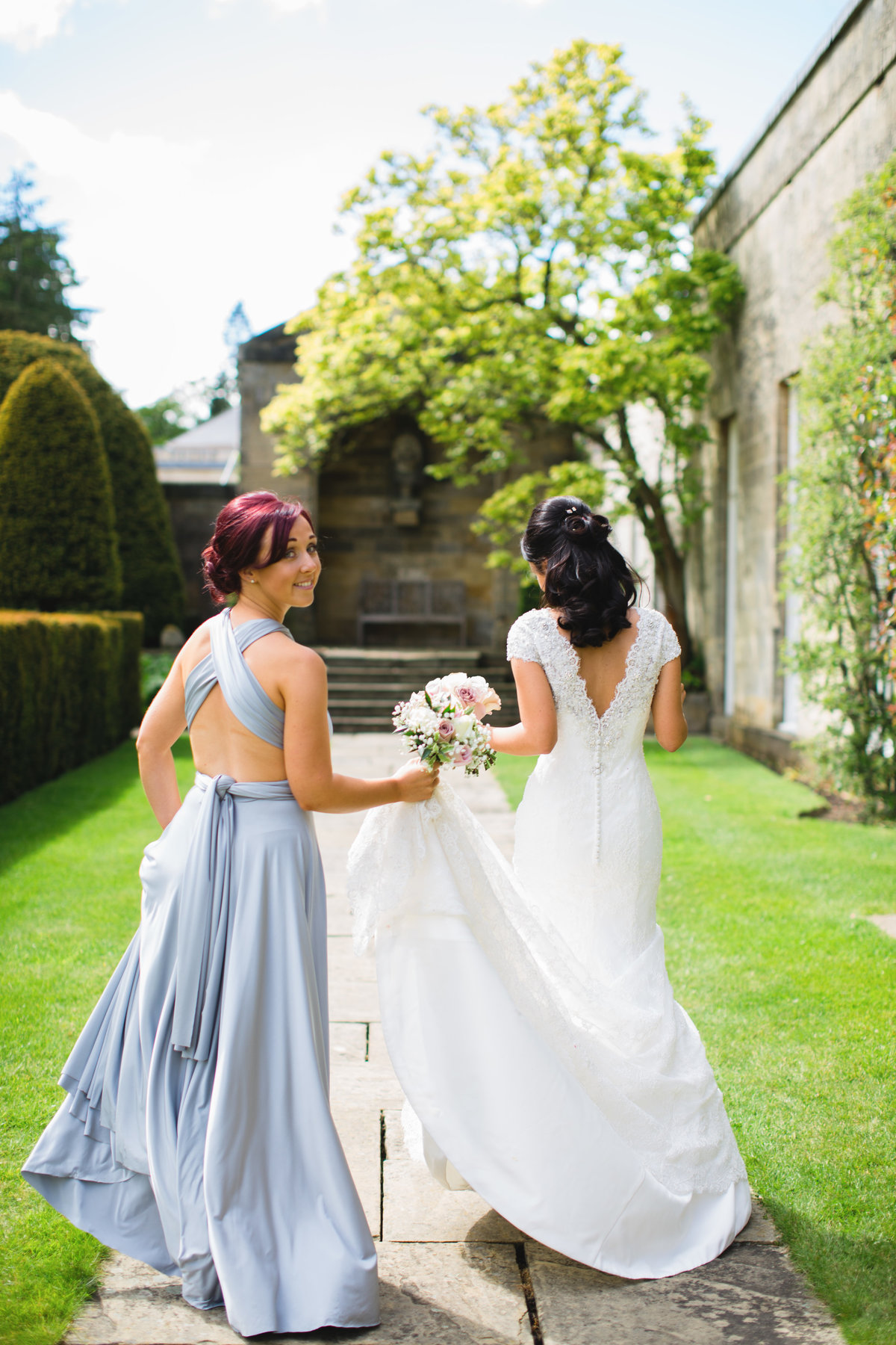 bride walking with bridesmaid in silver dress at rudding park looking backwards