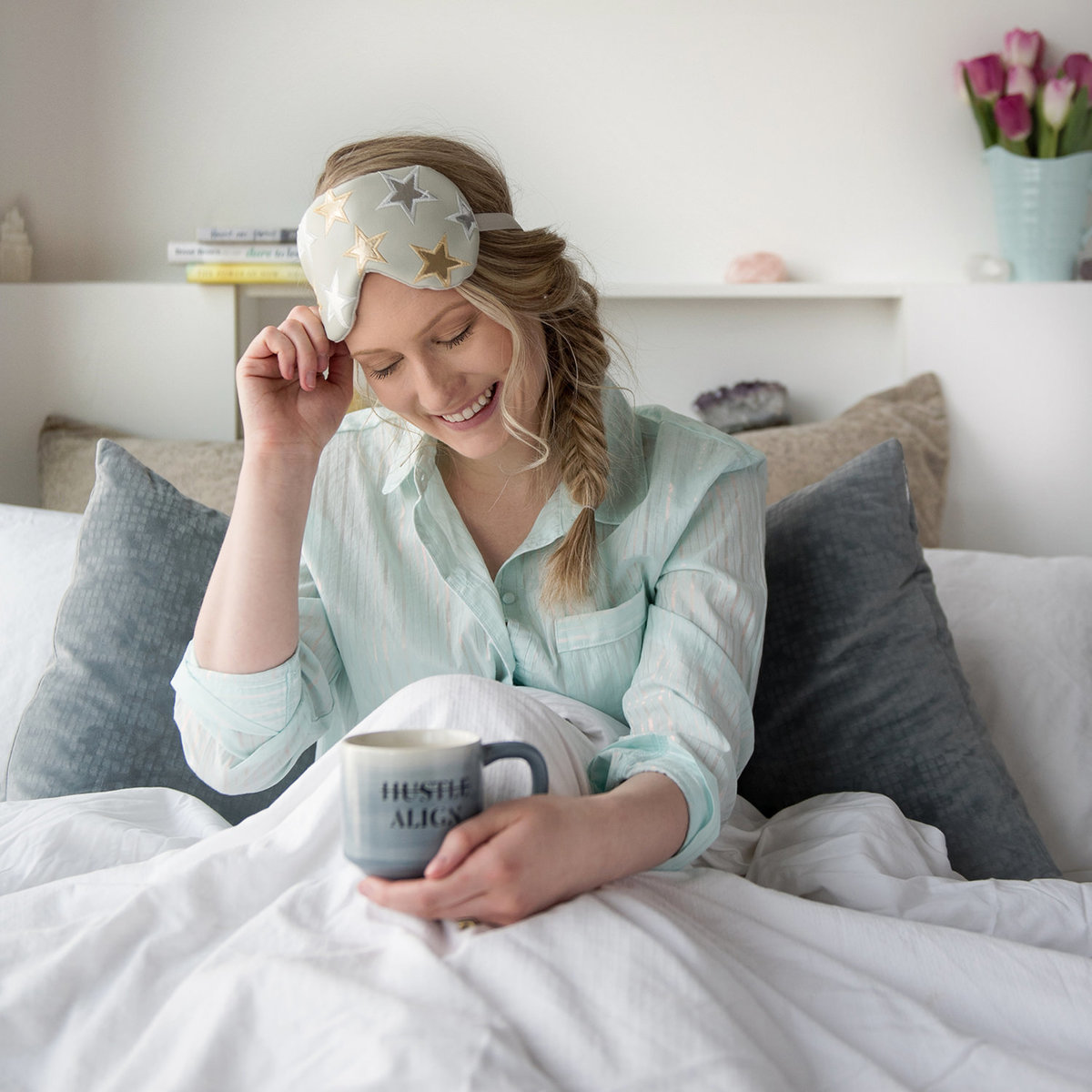 Woman in bed with coffee cup waking up